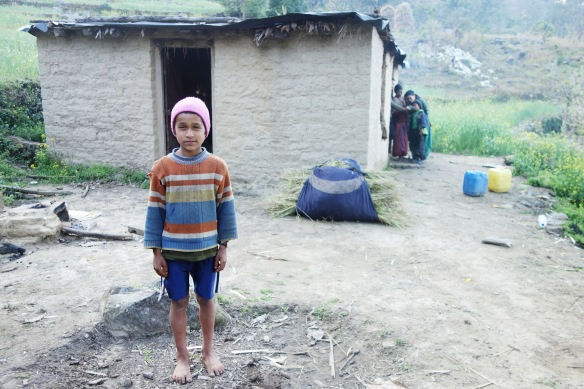 Behind this boy is his house, the house I stayed with during my four days in the village.