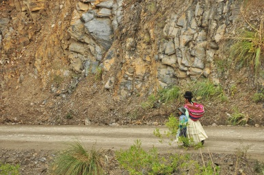 A typically dressed lady walking with her son.