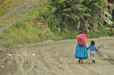 A lady and her son walking down the road.